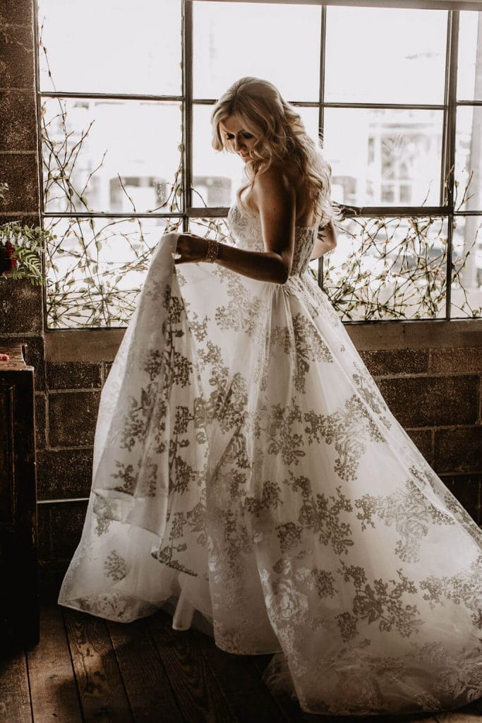 Bride in front of window with tattoos and texture wedding gown