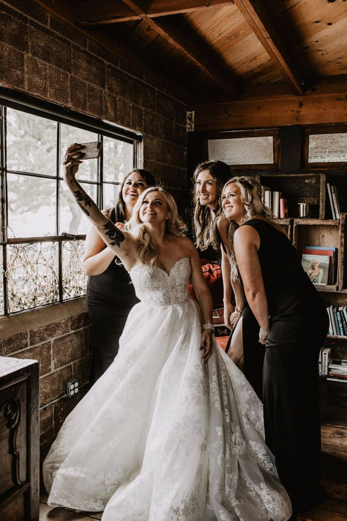Bride takes selfie with bridesmaids in all black with tattoos