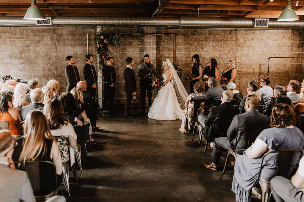 Cool industrial wedding against a brick wall at Smoky Hollow Studios. Bride and groom with tattoos and moody florals.