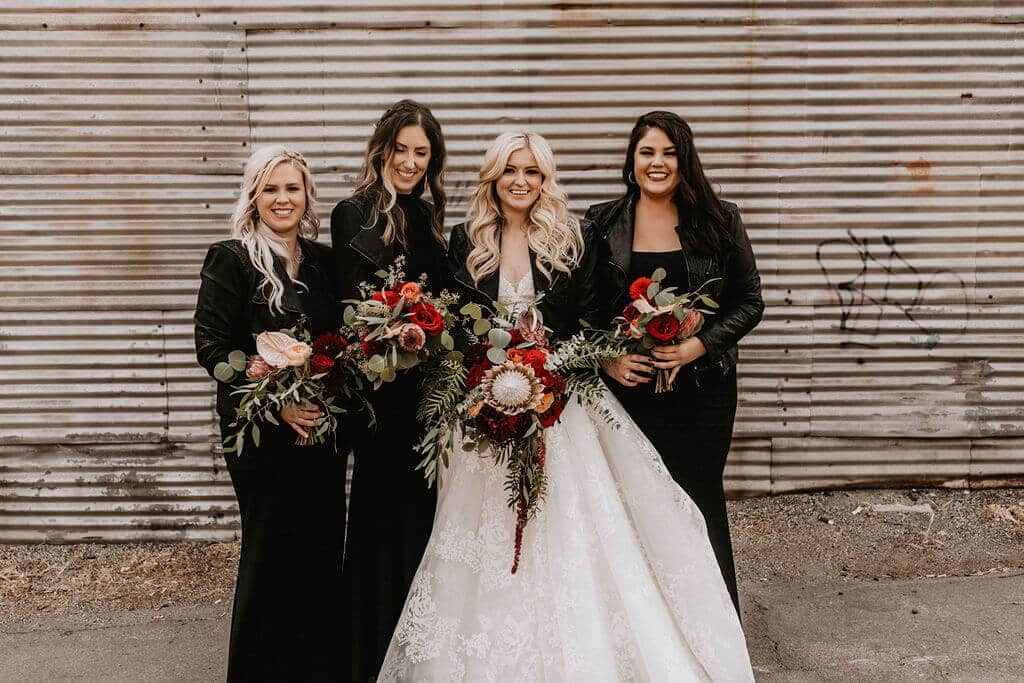 Bride and bridesmaids in leather jackets and moody bouquet at industrial warehouse venue Smoky Hollow Studios