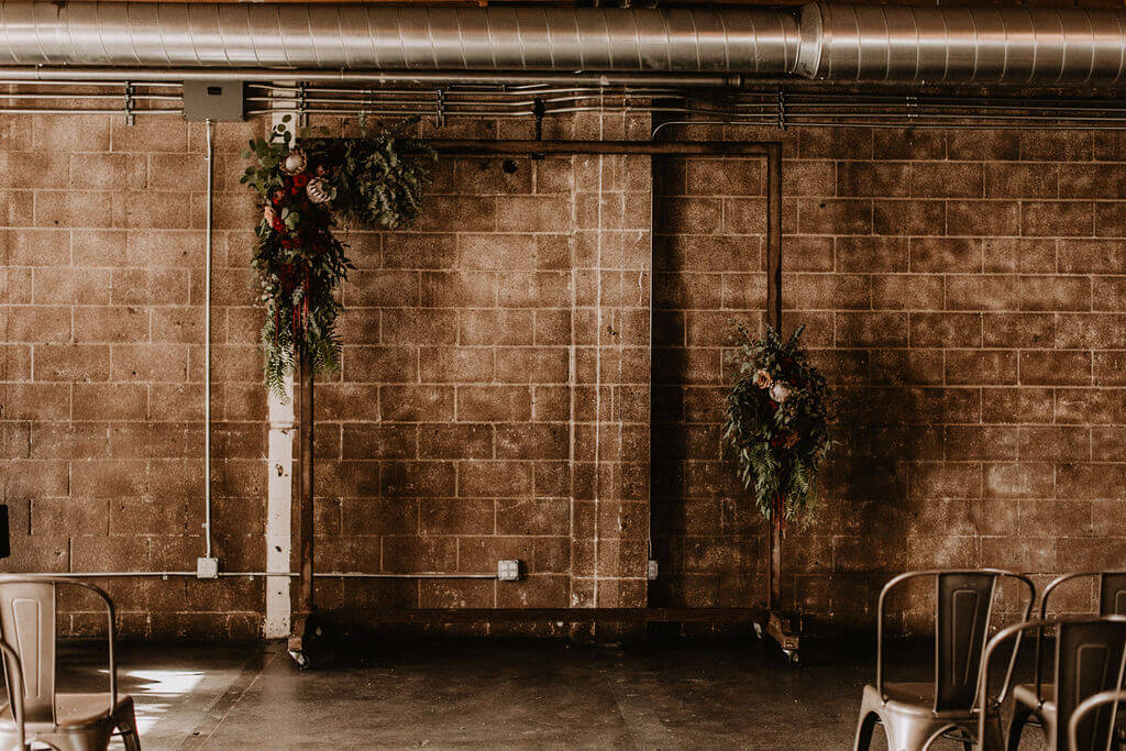 Metal arch with dark florals and deep reds against brick wall at Smoky Hollow Studios