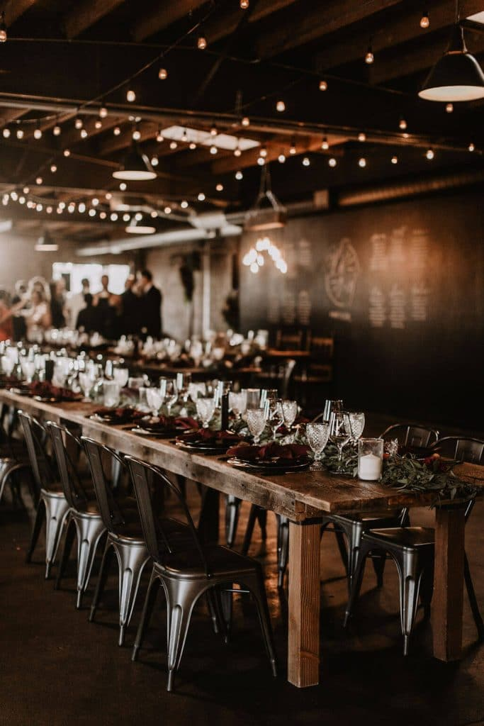 Long wooden tables with green garland for moody alternative industrial wedding at Smoky Hollow Studios