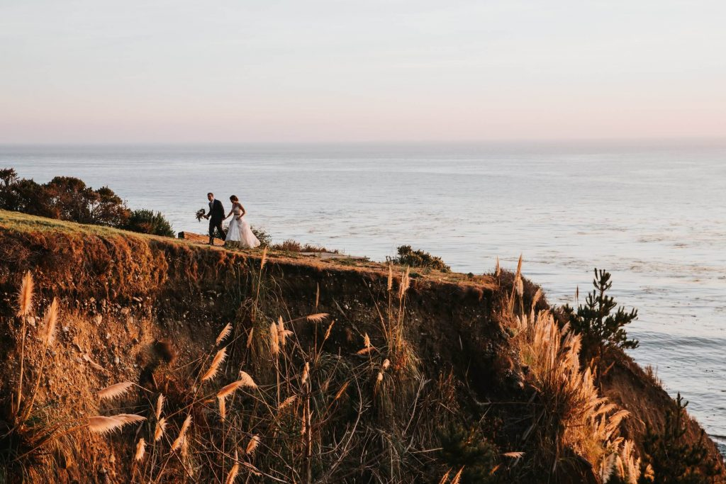 Bride and groom on the cliffside near the ocean in Big Sur, California for an intimate and  romantic wedding day