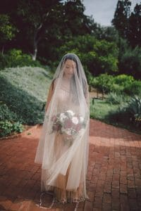 Romantic couple photos on their wedding day with a full length veil and champagne beaded wedding dress.