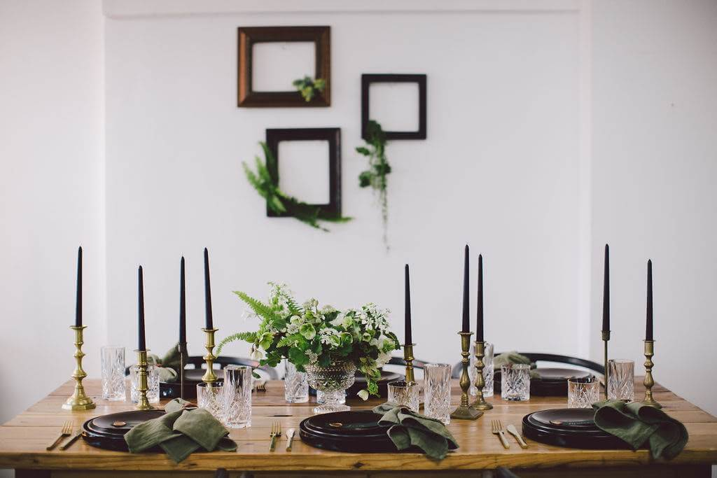 Black candlesticks, black plates and green napkins on wood table. Greenery hanging from frames for trendy dinner party. Eco friendly wedding idea