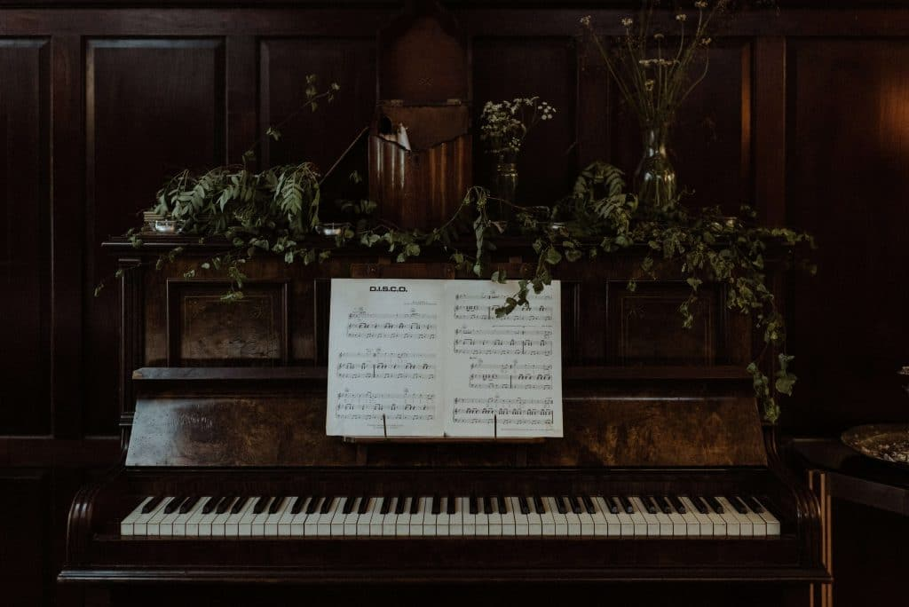 Old piano with greenery in old manor in Scotland. Wedding at Inshriach House in Inverness Scotland. Bride and groom got married by the river and had an intimate reception for 35 guests inside the manor.
