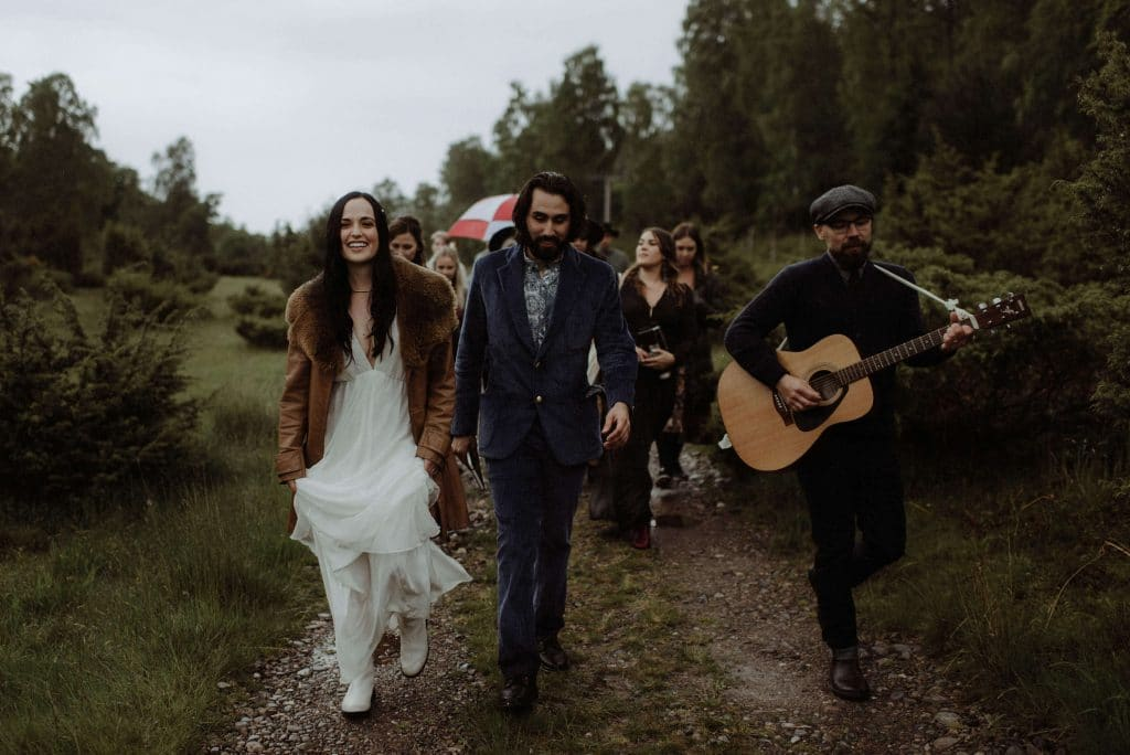 Wedding in Inverness Scotland. Bride and groom walk down to the river for intimate ceremony with guitar player in the rain.