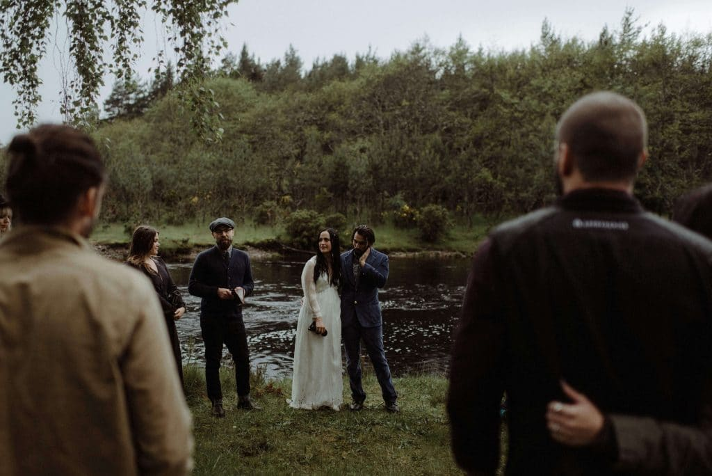 Wedding at Inshriach House in Inverness, Scotland. Bride and groom and guests have ceremony down at the river