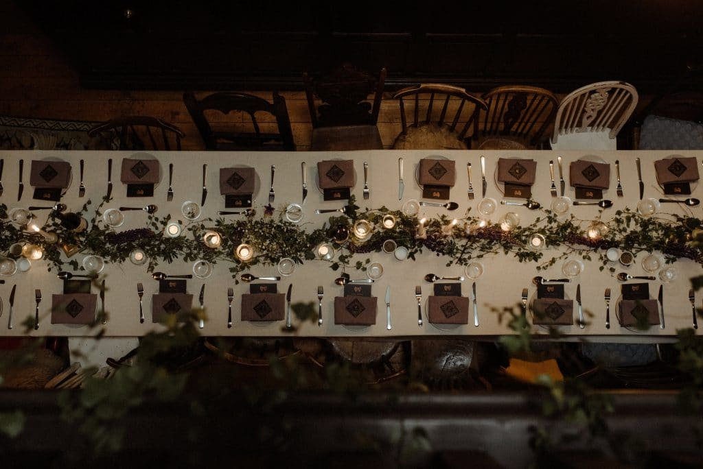 Long table with lots of candles and green garland with wildflowers for moody wedding in Scotland.