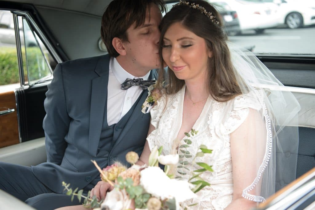 A bride and groom sit in the back of a vintage car on their wedding day in Palos Verdes