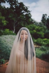 Beautiful bride with a full length veil on her wedding day complete with a champagne beaded wedding dress