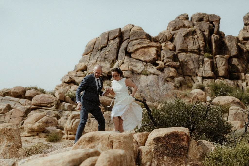 A bride and groom hike through Joshua Tree for their wedding photos.