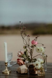 A whimsical floral arrangement on a wooden reception table for a desert wedding in California.