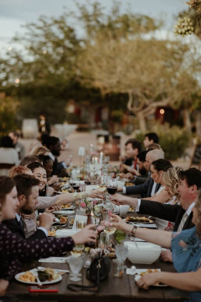 Guests sit for a fun wedding dinner in the desert at Rimrock Ranch.