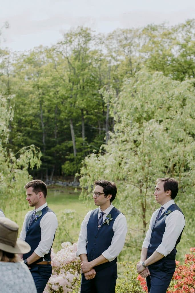 Groomsmen in a field for a summer wedding ceremony in mid coast Maine.
