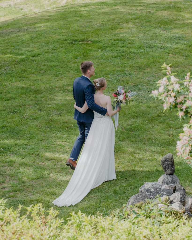 A bride and groom steal a moment to themselves during their summer Maine wedding.