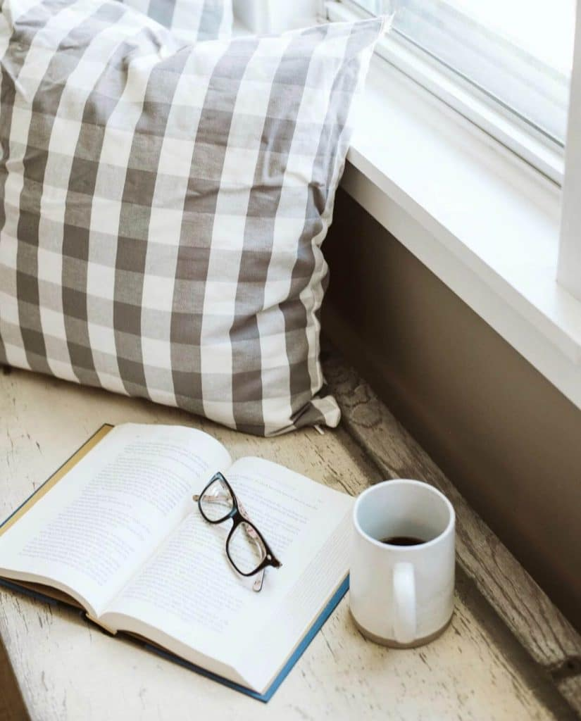 book by the windowsil with glasses and cup of coffee