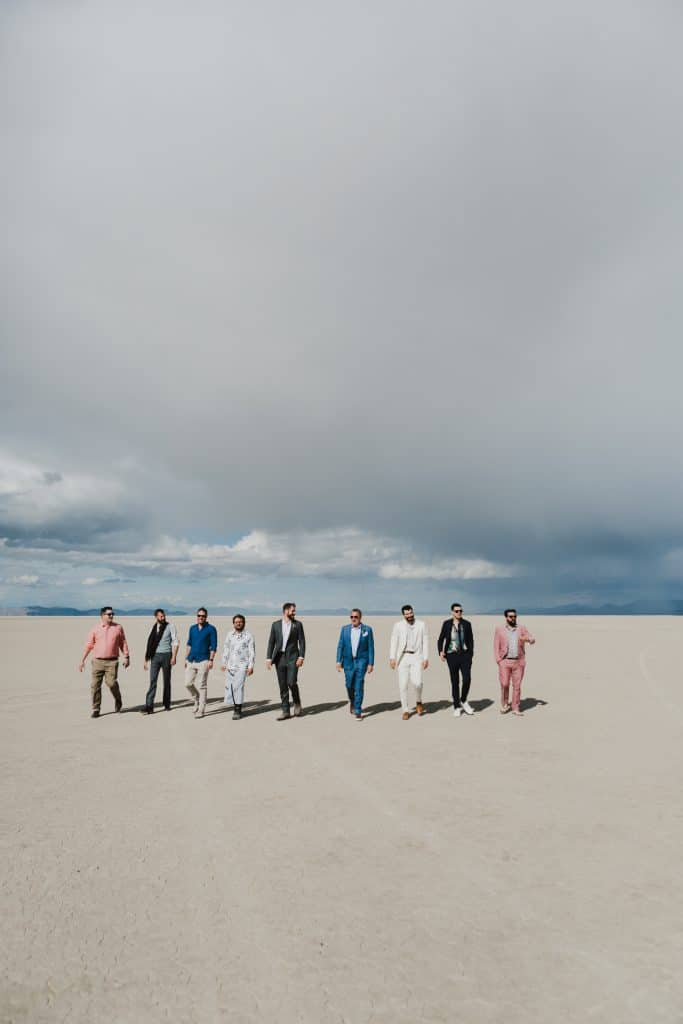 A groom and his groomsmen pose in the desert for a Burning Man wedding.