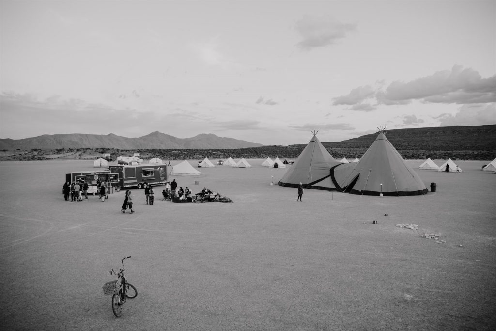 A remote desert wedding setup inspired by Burning Man with glamping tents by Stout Tent rentals