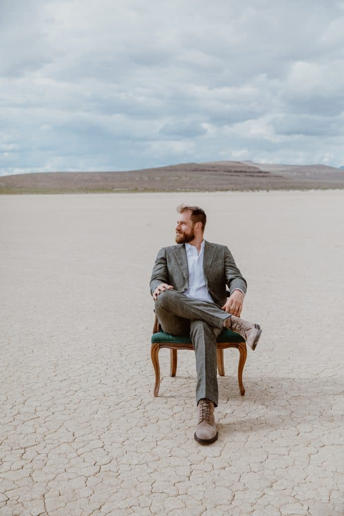 A groom poses in a chair in the middle of the desert before his boho style wedding ceremony.