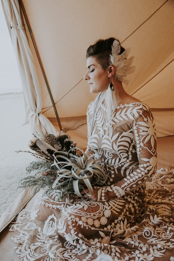 A bride with a creative feather hair piece and air plant bouquet poses in a clamping tent before her desert wedding ceremony.