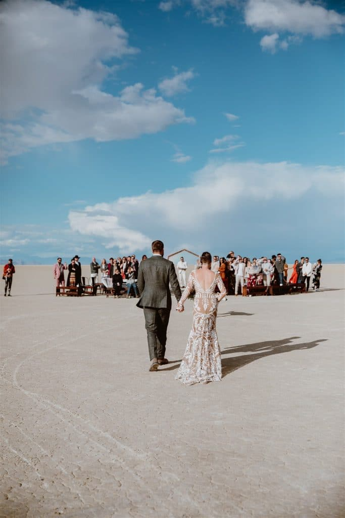 A bride and groom walk together to their ceremony in the desert with beautiful blue skies!