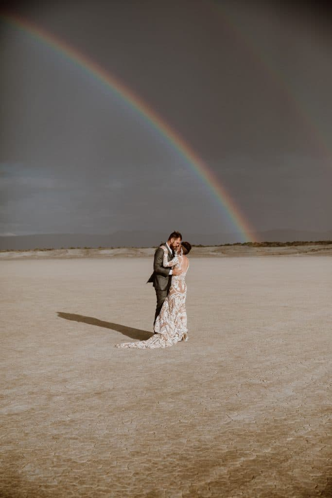 A bride and groom stand under a double rainbow in the desert for a festival style wedding inspired by Burning Man.