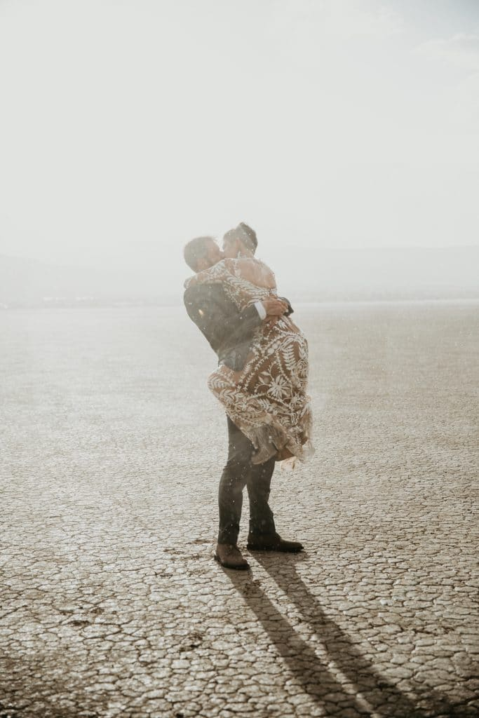 A bride and groom kiss each other during a surprise rain shower in the desert.