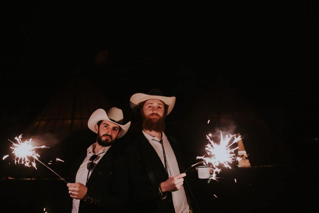 Two wedding goers dressed in cowboy outfits with sparklers during a Burning Man inspired wedding in the desert.