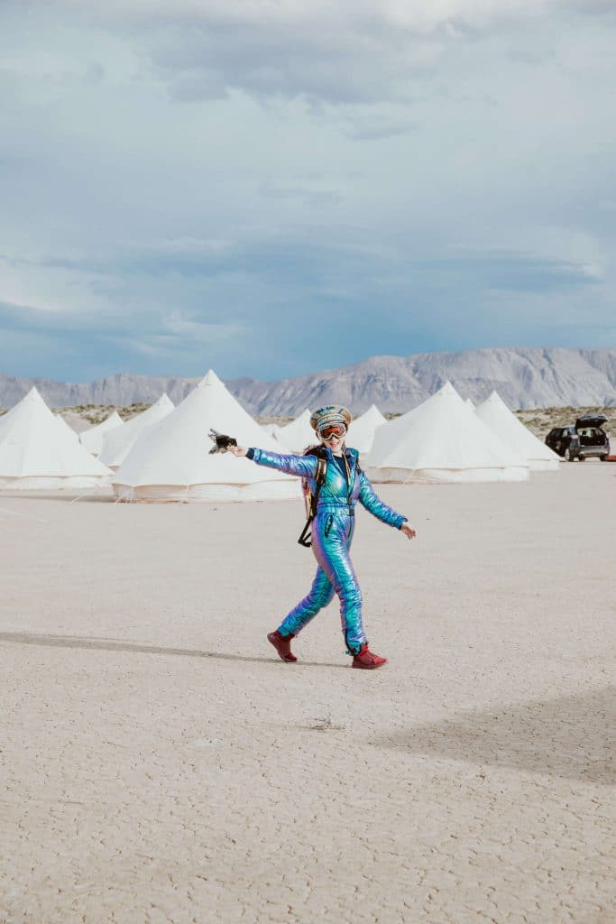 A guest for a Burning Man wedding wears a fun and creative outfit ini the desert.