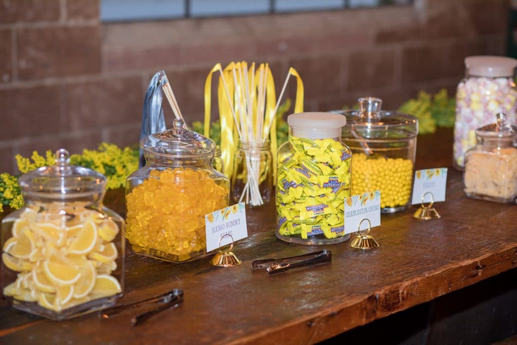 Fun candy table with yellow candies for late night dessert table at wedding