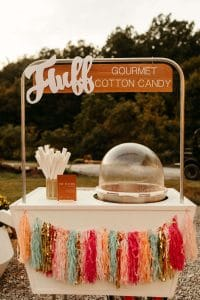 Cute cotton candy cart with colorful tassels. Fluff Nashville cotton candy cart at wedding at Under Canvas Smoky Mountains