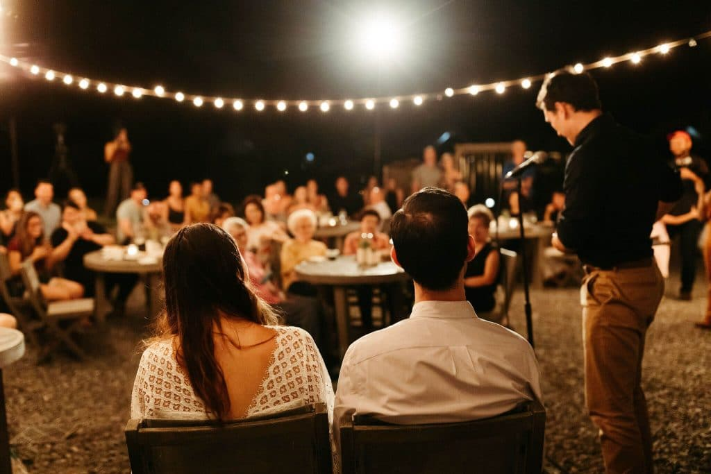 Bride and groom welcome toasts under the stars and market lights at under canvas smoky mountains