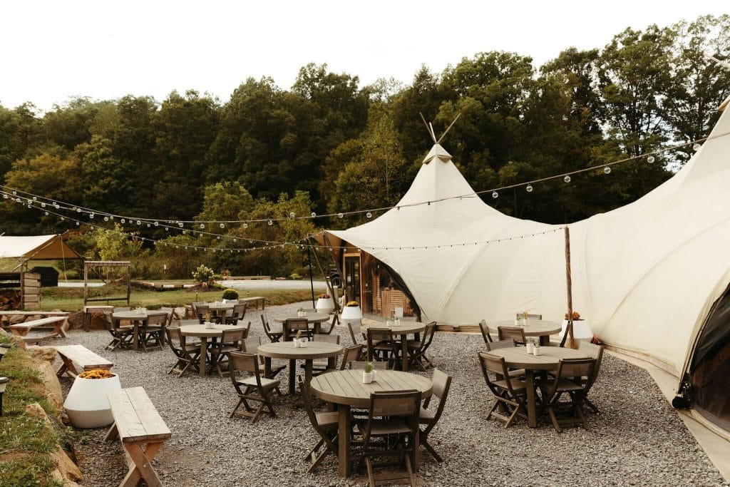 Teepee at Under Canvas Smoky Mountains with wooden tables and cute succulent centerpieces for wedding welcome party