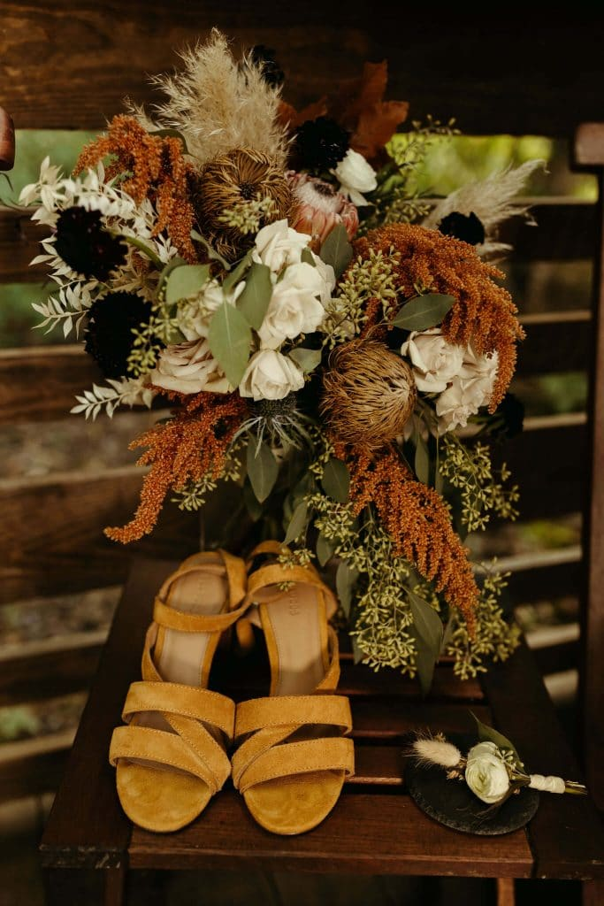 Gorgeous fall color bouquet with burnt oranges, green and whites for wedding at Under Canvas Smoky Mountains