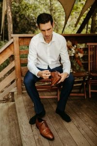 Groom getting ready at Under Canvas Smoky Mountains. Groom wearing white button down shirt, navy pants and light brown shoes