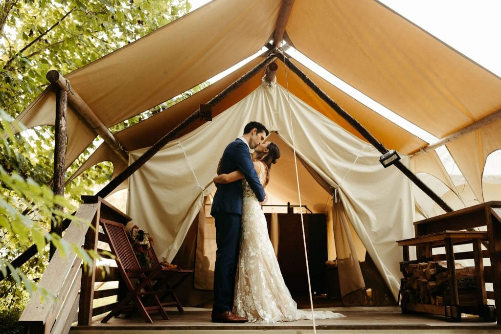 First look with bride and groom in front of tent at Under Canvas Smoky Mountains. Bride with long brown wavy hair and boho dress. Groom in dark navy suit and light brown shoes
