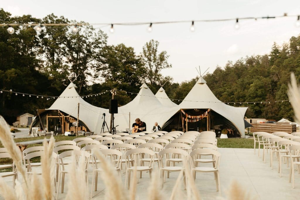 Pampass grass ceremony design and modern ivory chairs with teepee in the background for festival style wedding at Under Canvas Smoky Mountains