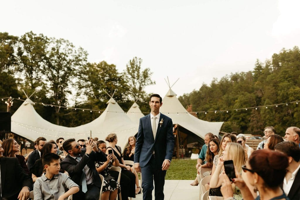Groom walking down the aisle with navy blue suit at Under Canvas Smoky Mountains