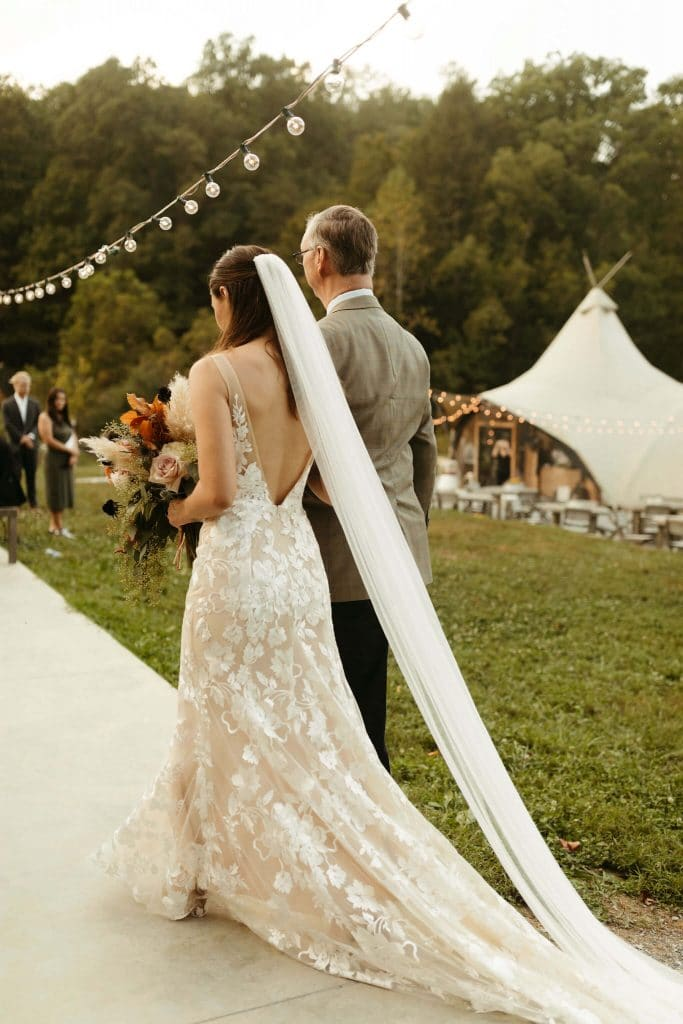 Bride with boho dress and long train and father walk down the aisle at Under Canvas Smoky mountains