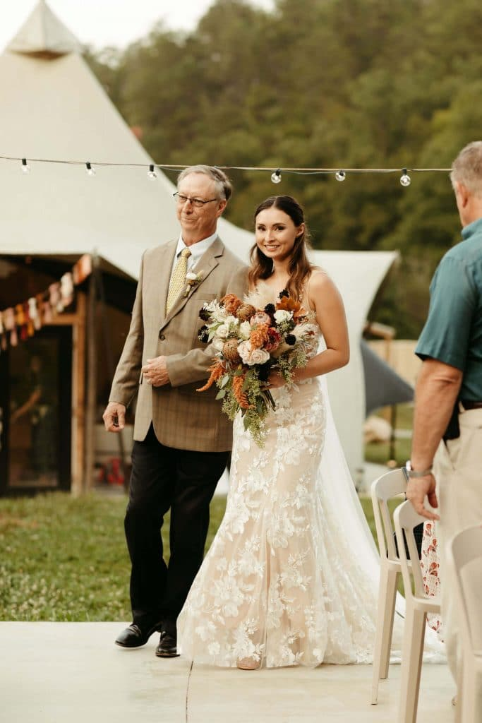 Bride with boho dress and long train and father walk down the aisle at Under Canvas Smoky mountains. Boho bride carrying fall bouquet with colorful tassels hanging from tent entrance