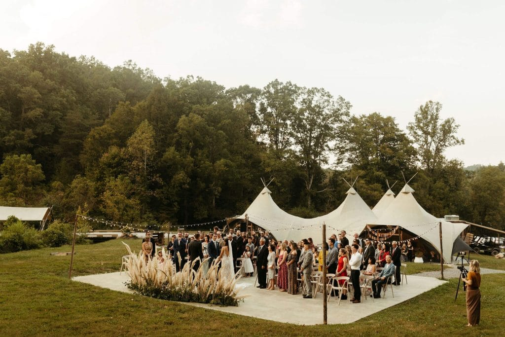 Ceremony set up with pampass grass and modern white chairs at Under Canvas Smoky Mountains. Festival style wedding in the great smoky mountains