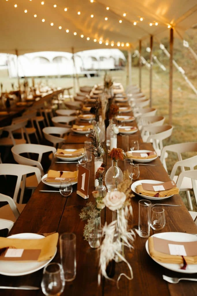 Long wooden tables with white plates, boho bud vases with pampass grass and mustard yellow napkins. Festival wedding at Under Canvas Smoky Mountains.