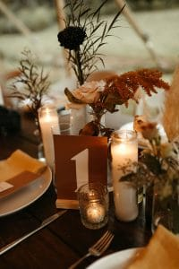 Dark orange modern table number with pampass grass flowers and tall candles