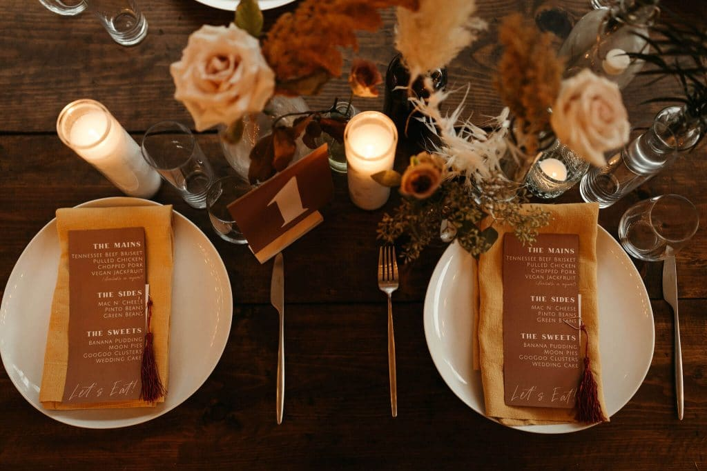 Long wooden tables with white plates, boho bud vases with pampass grass and mustard yellow napkins. Festival wedding at Under Canvas Smoky Mountains. Fall color florals with tall candles.