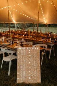 Seat Yo Self wedding seating chart sign. Long wooden tables with white plates, boho bud vases with pampass grass and mustard yellow napkins. Festival wedding at Under Canvas Smoky Mountains.