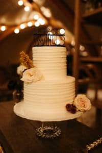 Simple white 2 tier cake with boho flowers and Let's Go Wild cake topper