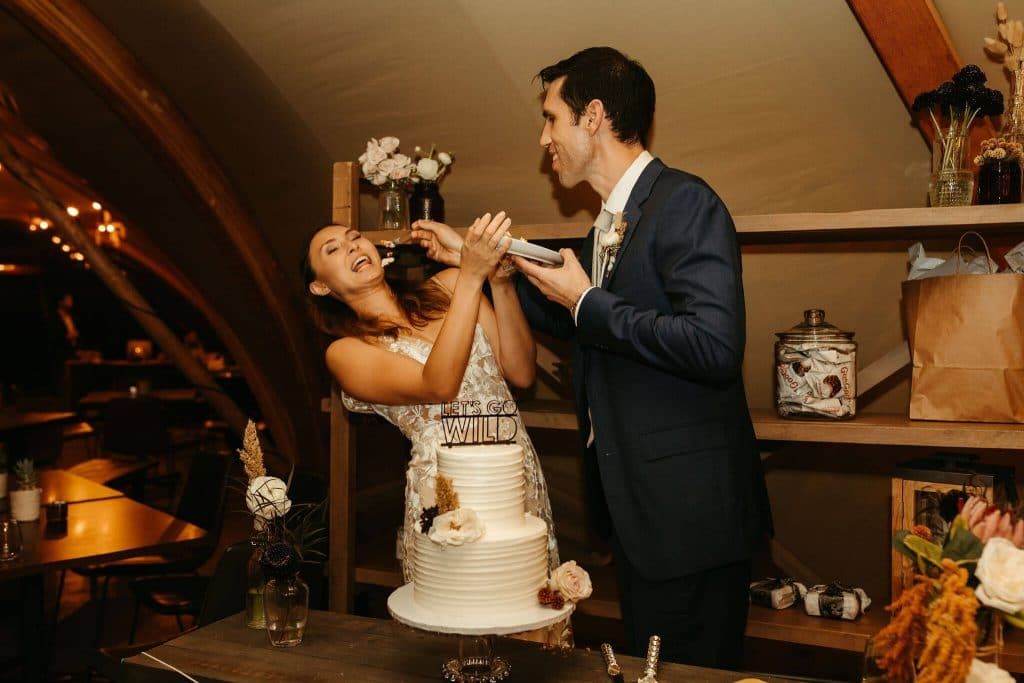 Couple smashes cake at Under Canvas smoky mountains
