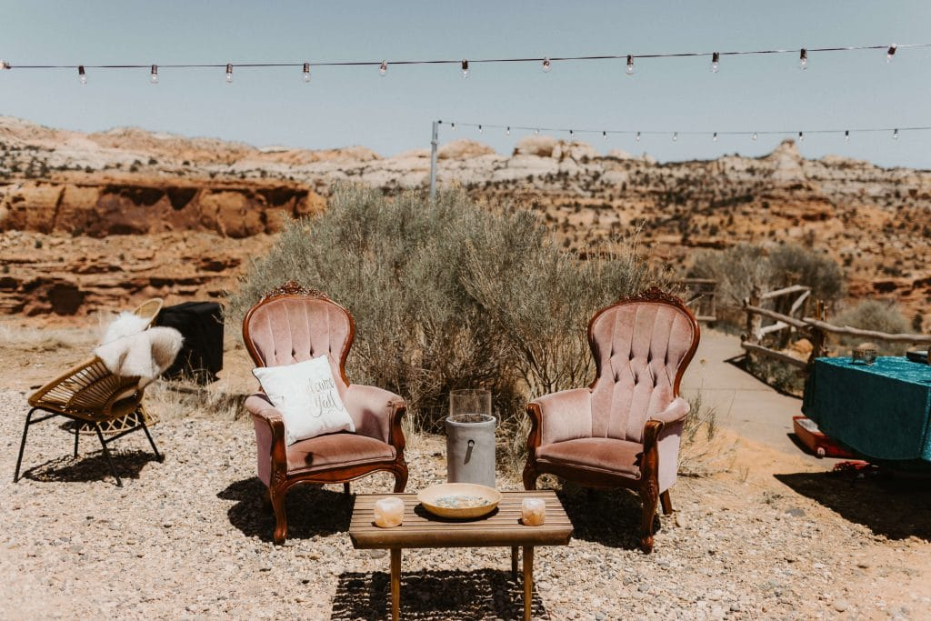 Set of pink velvet chairs in the middle of the desert for wedding at Kiva Koffeehouse in Escalante, Utah