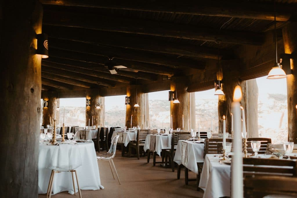 Intimate wedding reception set up at Kiva Koffeehouse in Escalante Utah. Tables of 4 with white linens, terrarium and gold chargers
